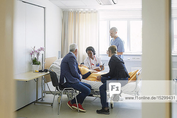 Mediziner diskutieren mit der Patientin und ihren Freunden auf der Station im Krankenhaus
