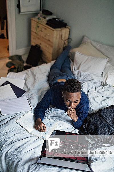 Hochwinkelansicht eines Teenagers  der ein Buch liest  während er den Laptop zu Hause am Bett benutzt Hochwinkelansicht eines Teenagers, der ein Buch liest, während er den Laptop zu Hause am Bett benutzt