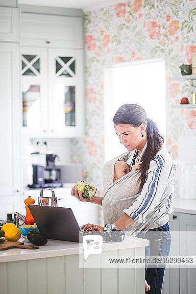 Berufstätige Mutter mit Tochter bereitet sich auf den Food-Blog vor  während sie zu Hause auf der Kücheninsel einen Laptop benutzt