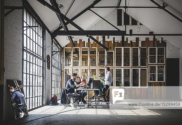 Geschäftsleute beim Brainstorming im Sitzungssaal während einer Besprechung am kreativen Arbeitsplatz