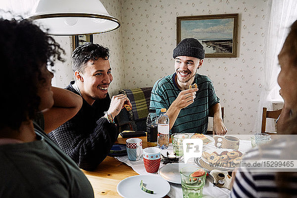 Cheerful friends talking while enjoying food in social gathering at home