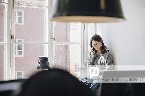 Lächelnde junge Programmiererin spricht über Handy  während sie im Kreativbüro den Laptop am Fenster benutzt Lächelnde junge Programmiererin spricht über Handy, während sie im Kreativbüro den Laptop am Fenster benutzt