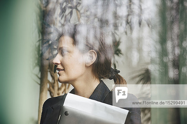 Zuversichtliche Geschäftsfrau  die durch ein Fenster im Büro wegsieht