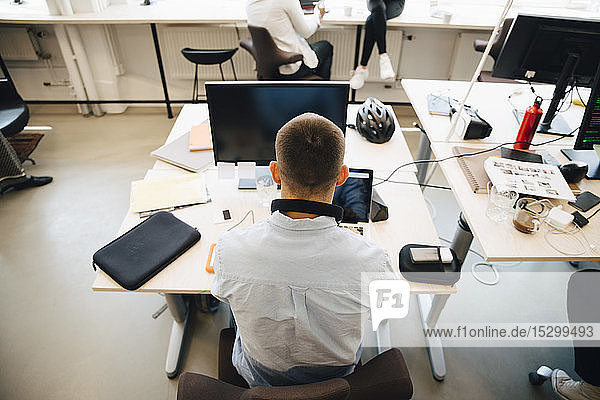 Rear view of male computer programmer using laptop on desk while sitting in creative office