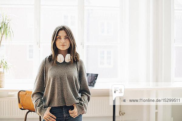 Porträt einer Computerprogrammiererin mit Kopfhörer  die im Büro vor einem Fenster steht