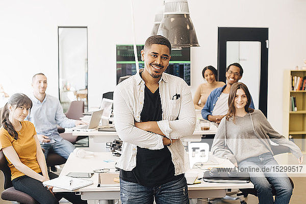Portrait of confident computer hacker with arms crossed standing while happy colleagues sitting at desk in office