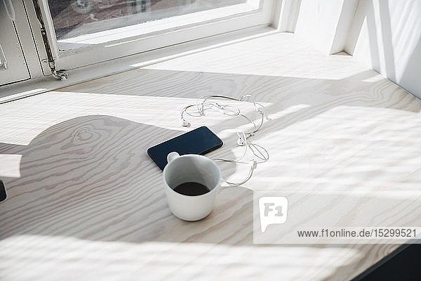 Hochwinkelansicht von Smartphone und Kopfhörer mit Kaffeetasse auf dem Schreibtisch am Fenster im Büro