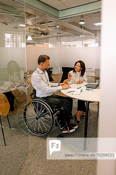 Lächelnde Geschäftsfrau bespricht Verkaufspläne mit behindertem Manager  während sie im Sitzungssaal sitzt