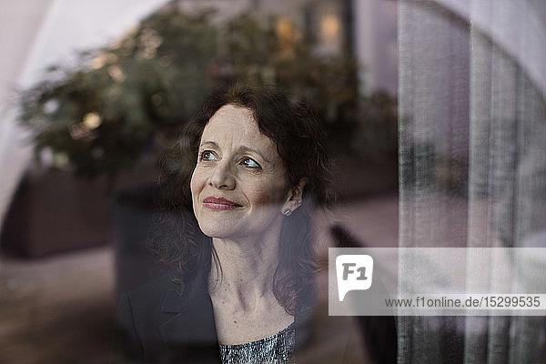 Nachdenkliche Geschäftsfrau schaut durch Glasfenster weg Nachdenkliche Geschäftsfrau schaut durch Glasfenster weg