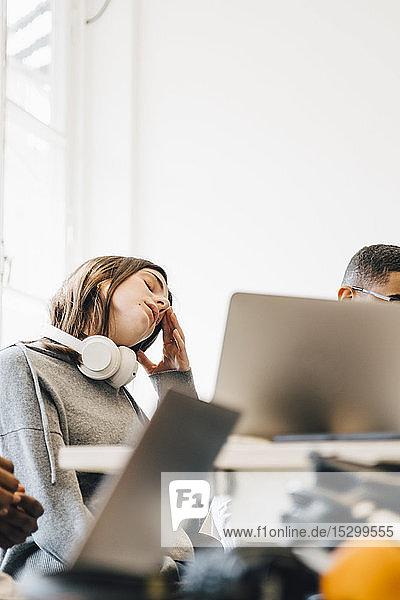 Erschöpfte Computerhackerin sitzt am Schreibtisch im Büro Erschöpfte Computerhackerin sitzt am Schreibtisch im Büro