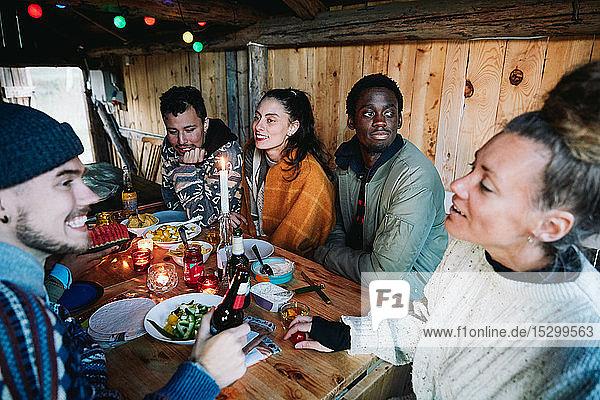 Männliche und weibliche Freunde unterhalten sich beim Essen auf dem Tisch im Blockhaus