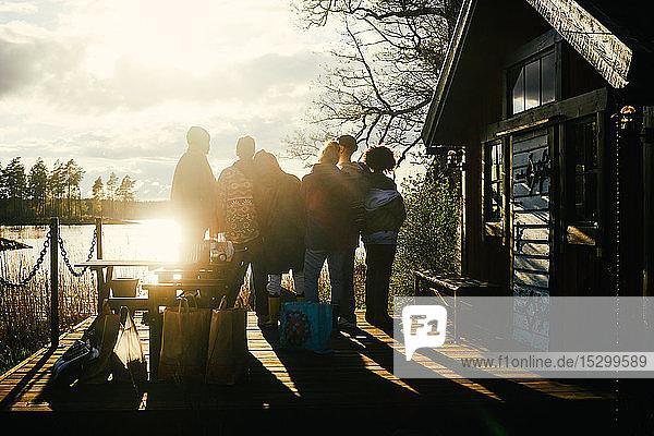 Scherenschnitt-Freunde schauen auf den See  während sie bei Sonnenuntergang vor dem Ferienhaus vor bewölktem Himmel stehen
