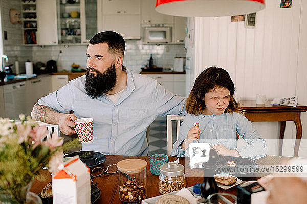 Father having drink while daughter making face during breakfast at home