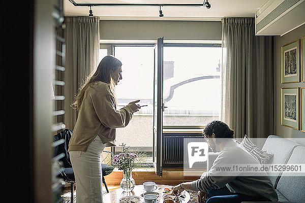 Paar im Hotelzimmer  Frau beim Fotografieren des Frühstückstabletts