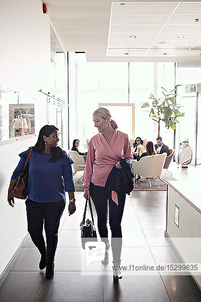 Geschäftsfrauen unterhalten sich beim Verlassen des Büros mit im Hintergrund sitzenden Kollegen Geschäftsfrauen unterhalten sich beim Verlassen des Büros mit im Hintergrund sitzenden Kollegen