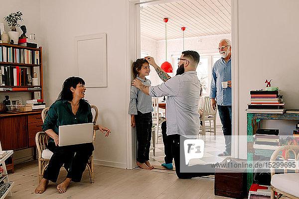 Glückliche Familie schaut auf einen Mann  der die Größe seiner Tochter am Eingang an der Wand misst