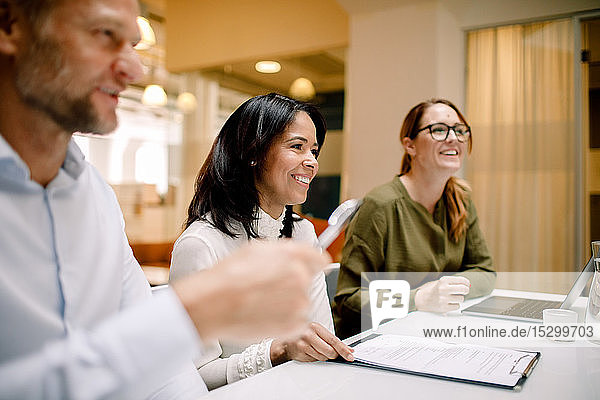 Lächelnde Geschäftskollegen arbeiten  während sie im Büro am Konferenztisch sitzen