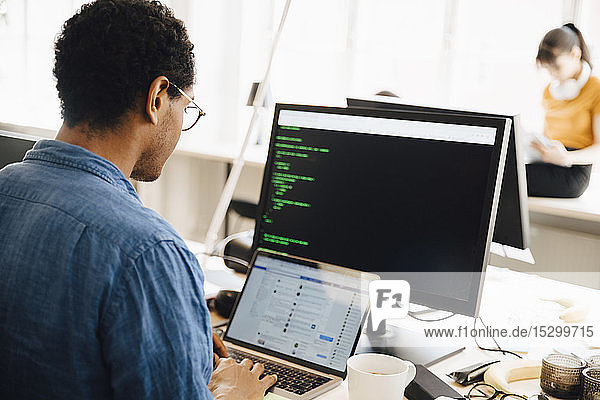 Male computer hacker using laptop on desk while sitting in creative office
