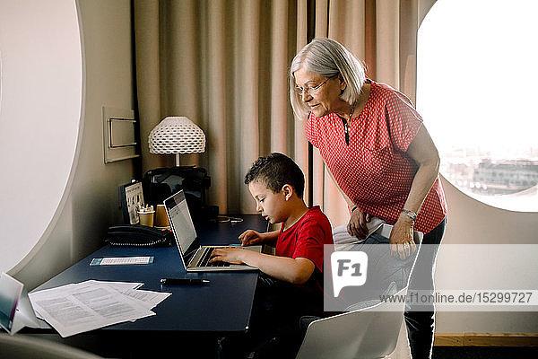 Großmutter sieht ihren Enkel am Laptop an  während sie im Hotelzimmer am Tisch sitzt Großmutter sieht ihren Enkel am Laptop an, während sie im Hotelzimmer am Tisch sitzt