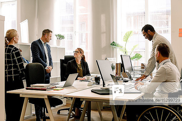 Geschäftsleute arbeiten gemeinsam am Schreibtisch im Büro