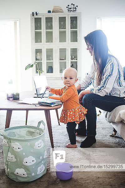 Porträt eines kleinen Mädchens mit beschäftigter berufstätiger Mutter im Wohnzimmer im Heimbüro