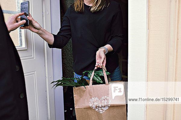 Mittendrin eine Frau  die dem Lieferanten ein Smartphone zeigt  während sie eine Pflanztüte an der Tür hält