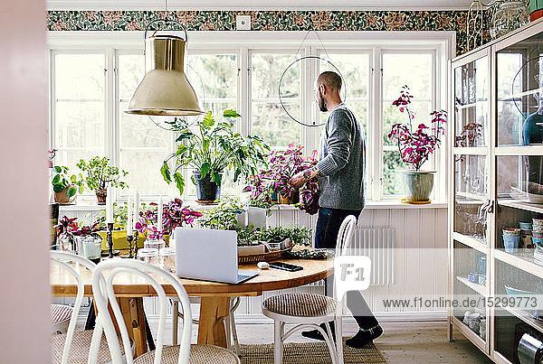 Mann in voller Länge im Zimmer zu Hause pflanzen