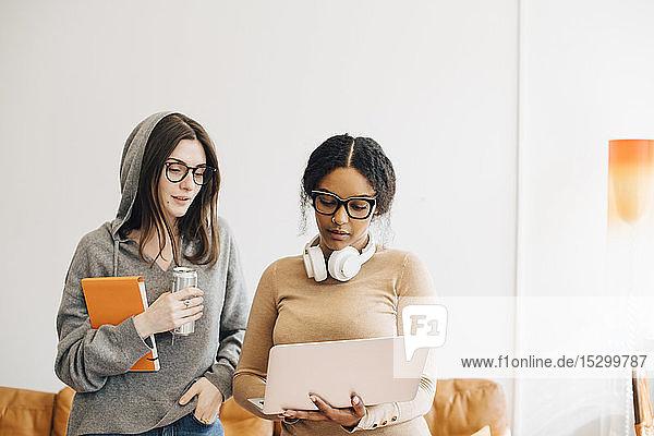 Computerprogrammiererinnen diskutieren über Laptop im Stehen im Büro