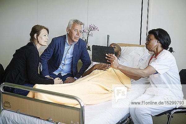 Ärztin zeigt Patientin und Familie im Krankenhaus medizinischen Bericht auf digitalem Tablett
