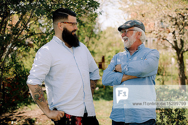 Happy father and son talking while standing in yard