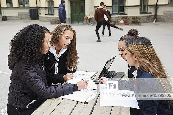 Multi-ethnische Freundinnen im Teenageralter lernen bei Tisch auf dem Schulhof Multi-ethnische Freundinnen im Teenageralter lernen bei Tisch auf dem Schulhof