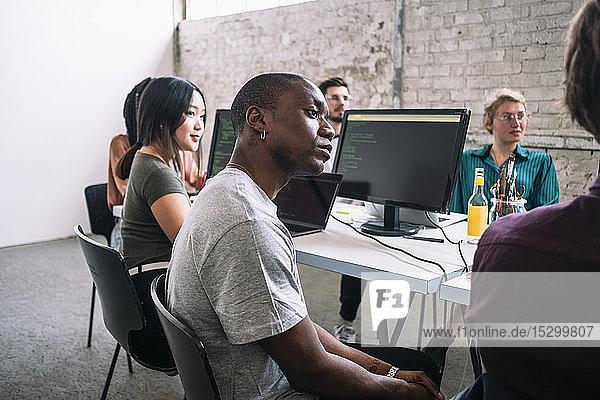 Selbstbewusste männliche und weibliche IT-Fachleute sitzen während einer Sitzung am kreativen Arbeitsplatz im Sitzungssaal
