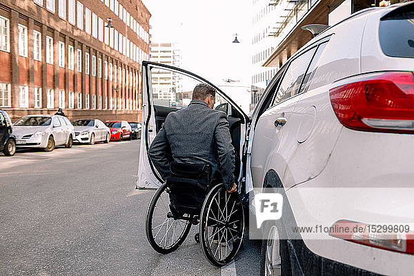 Rear view of mature man boarding white car while sitting on wheelchair in city