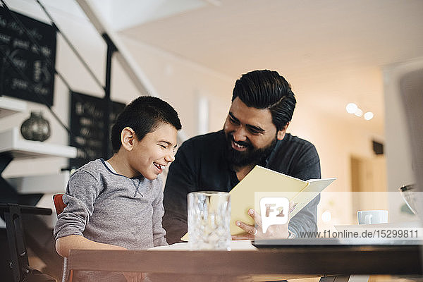 Smiling father teaching autistic son while sitting at table in house