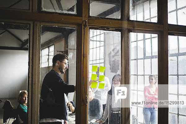 Junger männlicher IT-Programmierer teilt Geschäftsideen mit dem Team  während er auf Klebezettel zeigt  die durch eine Glaswand in