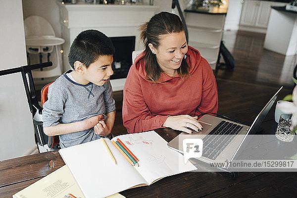 Lächelnde Mutter zeigt ihrem autistischen Sohn ein Video auf einem Laptop zu Hause
