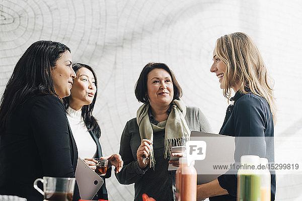 Weibliche Kollegen  die einer Geschäftsfrau bei einer Konferenz zuhören