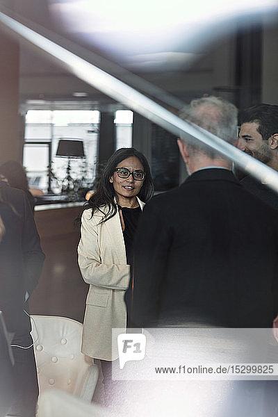 Geschäftsfrau spricht mit einem männlichen Kollegen  während sie in der Lobby im Büro steht und durch ein Fenster gesehen wird