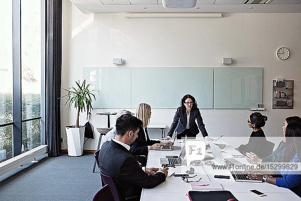 Geschäftsfrau interagiert mit Kollegen  die während einer Sitzung im Sitzungssaal am Konferenztisch sitzen