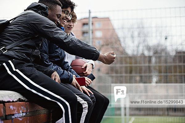 Glückliche männliche Freunde  die nach dem Basketballtraining im Winter auf der Stützmauer sitzen