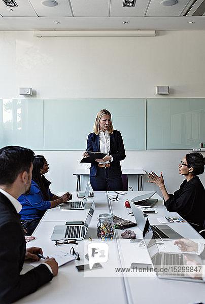 Kollegin interagiert mit Geschäftsfrau  die während eines Treffens mit Kollegen am Konferenztisch steht