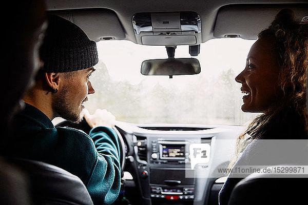 Männliche und weibliche Freunde unterhalten sich während einer Autofahrt