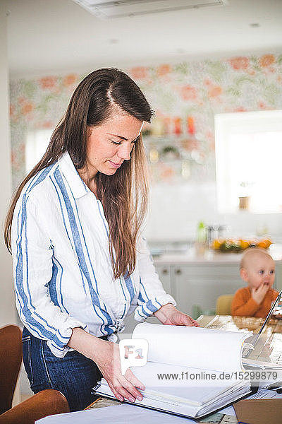 Busy female entrepreneur examining filed documents while daughter sitting in background at home office