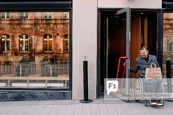 Behinderter reifer Mann mit Einkaufstasche verlässt Laden in der Stadt