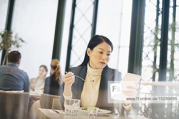 Confident businesswoman using digital tablet while eating lunch at cafeteria in office