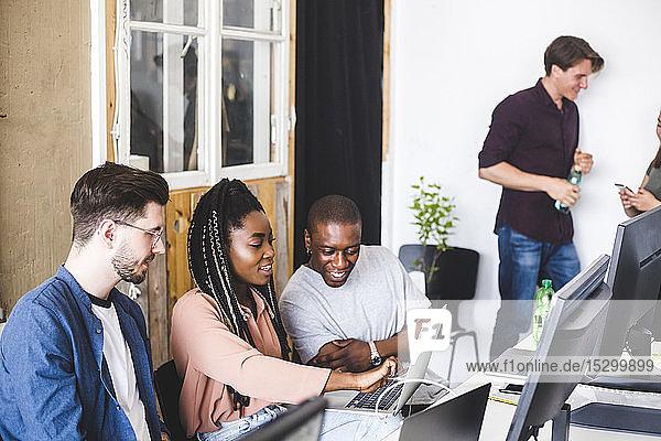 Weibliche IT-Expertin zeigt Laptop vor professionellen männlichen Hackern am Arbeitsplatz