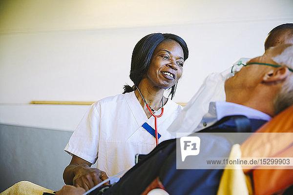 Lächelnde Ärztin betrachtet reife Patientin auf Bahre im Krankenhaus