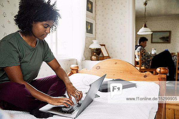 Young woman using laptop on bed while friend sitting in background at home