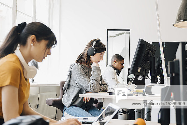 Side view of focused programmers using laptops on desk while sitting in office