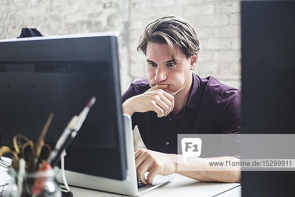 Besorgter professioneller Hacker betrachtet Laptop im Kreativbüro